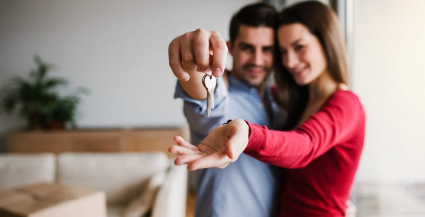 A young happy couple with a key and cardboard boxes standing indoors, moving in a new home.