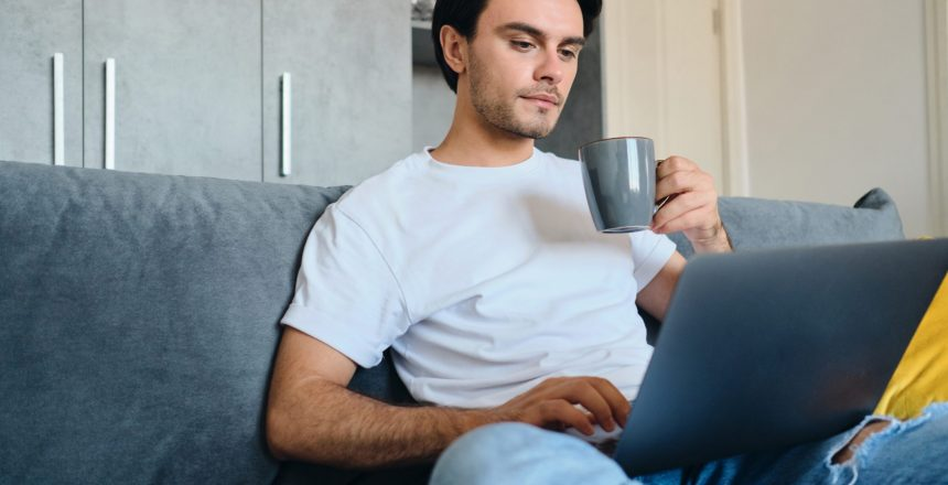 Young attractive brunette man in white T-shirt holding cup in hand thoughtfully working on laptop sitting on sofa at modern home