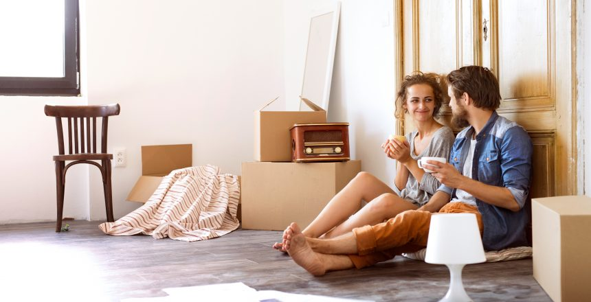 Young married couple moving in a new house, sitting on the floor at the old wooden door, drinking coffee, resting